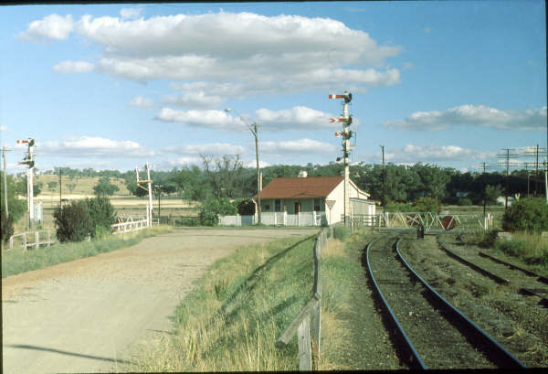 The scene in 1980 which shows the original Station Masters house and the manually operated gates. To the right the single line south and the left the up & down lines north.