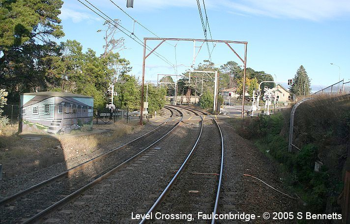 A view of the level crossing at Faulconbridge taken from the rear of a Sydney bound train. To the left of photo can be seen the Comms Hut which has been painted by April Keogh with a painting of Henry Parkes first house in Faulconbridge which is located nearby.