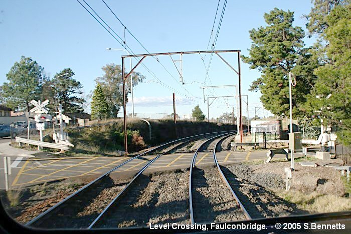 A view of the  level crossing at Faulconbridge taken from the rear of a Katoomba-bound train.