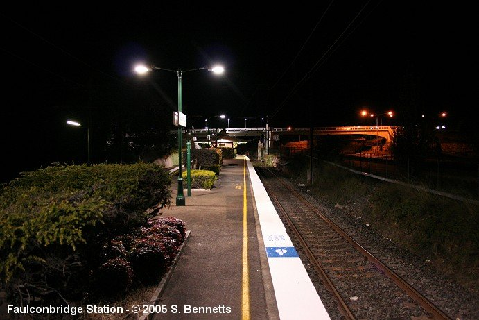 A night-time photo taken from the Sydney end of Faulconbridge platform 1 facing in a southerly direction looking along the Up main. The footbridge over the highway is visible in right of photo.