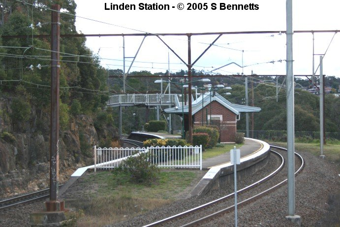 A photo taken looking in a westerly direction showing the Sydney end of platform and buildings at Linden and the tight radius of the curve it is built on. To the right and centre rear of the photo, the homes of residents of Linden can be seen through the maze of overhead wires and staunchions.