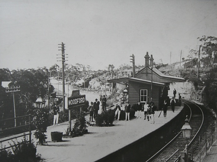 A photo of a photo held at National Trust's (NSW) Woodford Academy. It shows Woodford Station and the signal box which was removed in the late 1950's. The photo has been estimated to have been taken circa 1919, dated from the people and the items in the photo.  The original single line cutting dating back to 1867 and by passed by 1896 can be seen slightly above and to the right of the D on the Woodford sign on the platform. The original highway can also be seen behind this sign which now forms the lower carpark at Woodford Station. At least 2 station staff can also be seen in this photo.